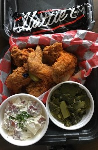 Hot wings, greens, and potato salad in a to-go box.