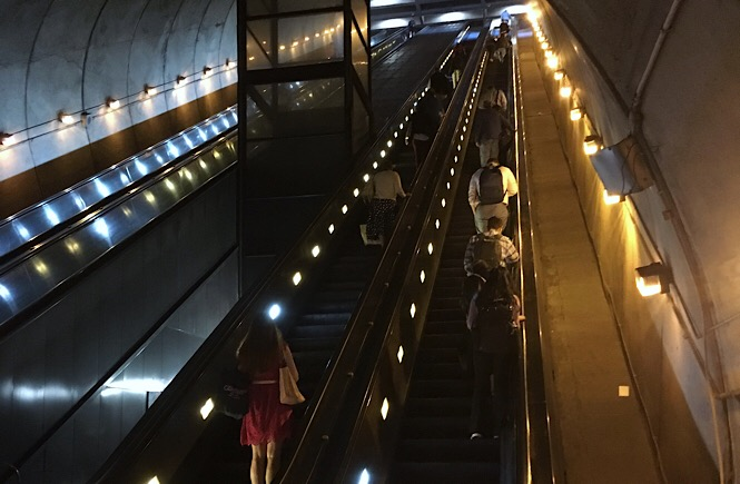 Photo of a large escalator staircase transporting patrons out of the underground system.