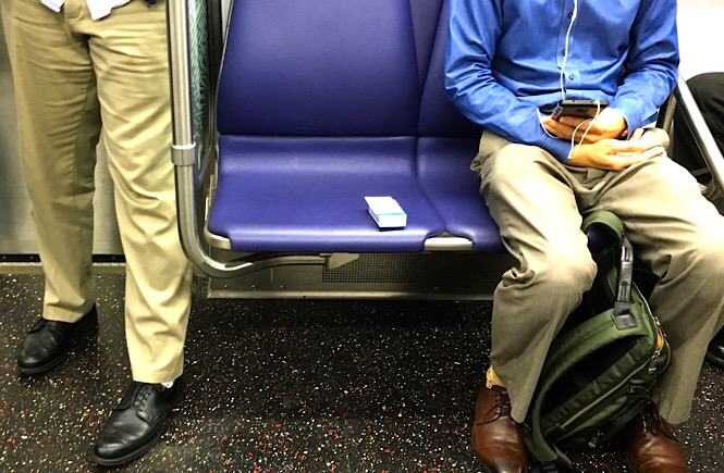 Photo of a small package of tissue on a metro car seat.
