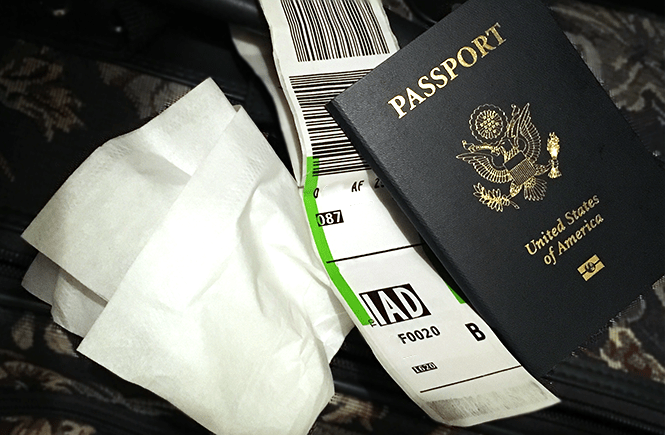 Photograph of a passport, luggage tag, and tissue on top of a suitcase. What to do if You're Traveling While Sick   Frolic & Courage