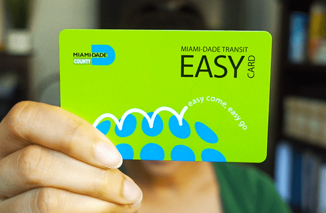 Closeup photo of me holding a bright green Mimai-Dade Transit Easy Card. Frolic & Courage.