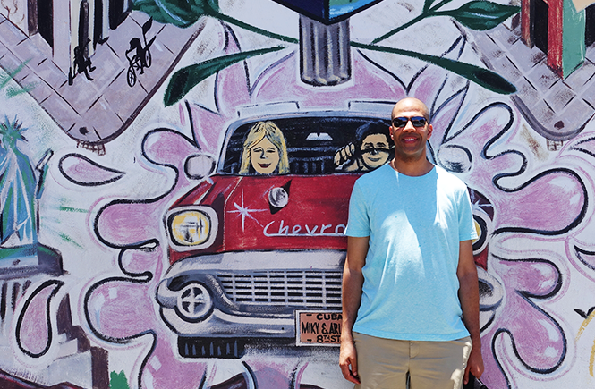 Photo of Kevin standing in front of Little Havana wall art.