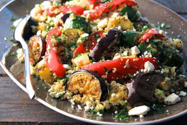 Mediterranean Quinoa and Grilled Vegetable Salad close-up shot on platter with gray border on a rough wood table