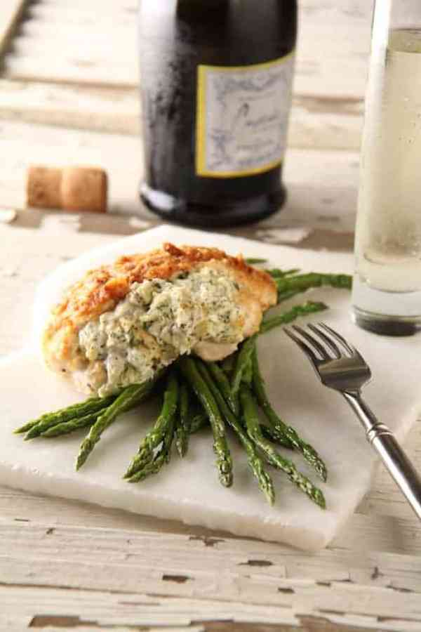 Crab-Stuffed Chicken Breasts - Hero shot of dish served on asparagus on white marble surface with champagne in the background