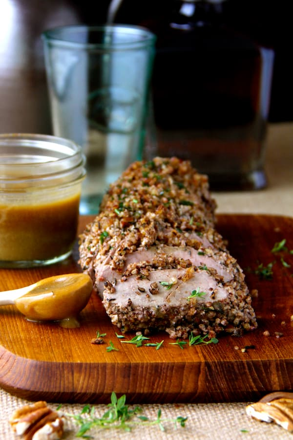 Pecan-Crusted Pork Tenderloin with Bourbon - Mustard Sauce - Straight-on close-up shot of pork tenderloin on wood cutting board with pecans and fresh thyme scattered around