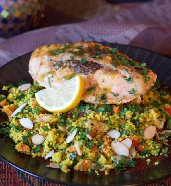 Chicken Marrakesh with Jeweled Couscous - Hero shot with chicken on bed of the couscous garnished with a lemon slice