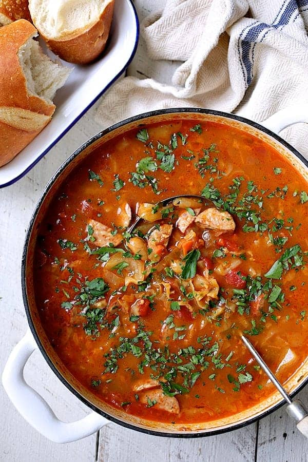 Farmhouse Cabbage Soup with Cannellini Beans and Kielbasa - Overhead hero shot of soup in white Dutch oven garnished with parsley