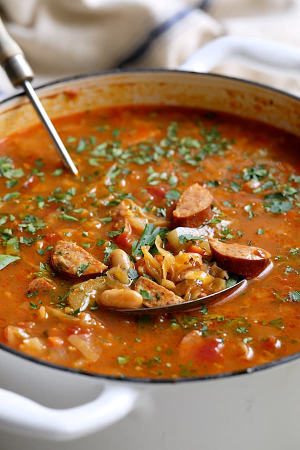 Farmhouse Cabbage Soup with Cannellini Beans and Kielbasa - Straight-on close-up shot of soup in white Dutch oven