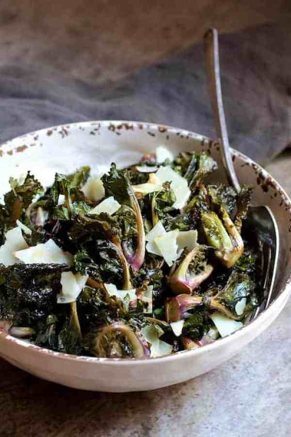 Balsamic Roasted Kale Sprouts with Shaved Parmesan - Hero shot of dish in white distressed bowl with serving fork on gray background