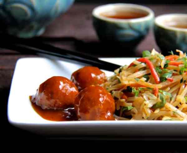 Hoisin Glazed Pork Meatballs and Rice Noodles with Cabbage and Carrots - Straight-on shot of dish on rectangular white plate with blue teacups in the background