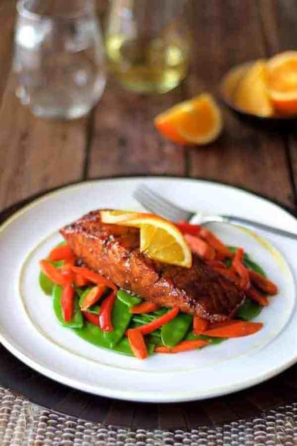 Pomegranate and Orange-Glazed Salmon with Stir-Fried Vegetables - Hero shot of dish on white plate garnished with orange wedge