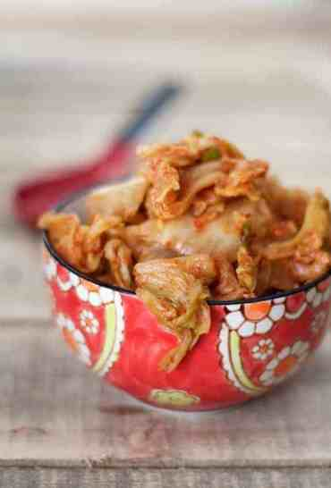 Homemade kimchi in decorative red bowl.