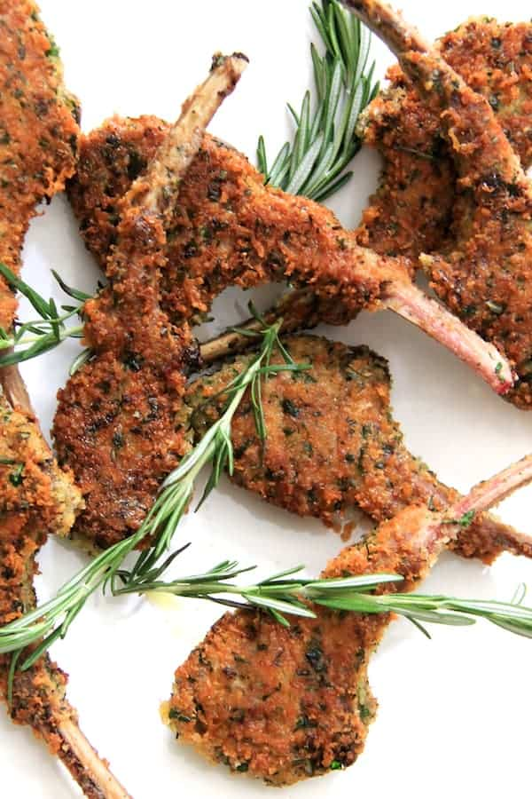 Parmesan and Herb Crusted Lamb Chops - Close-up shot on white background with scattered rosemary sprigs