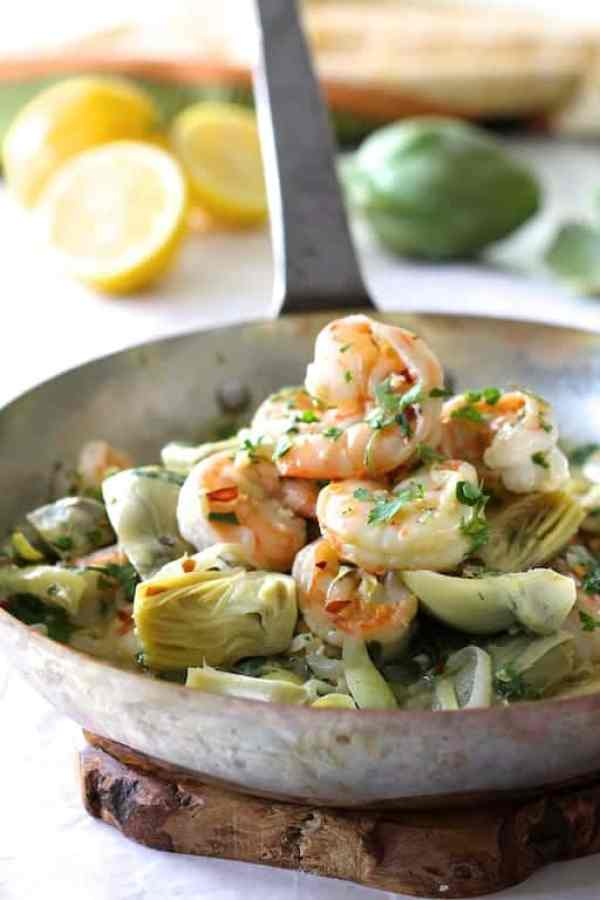 Shrimp Scampi with Artichokes - Hero shot of dish in skillet with lemons and artichokes in the background