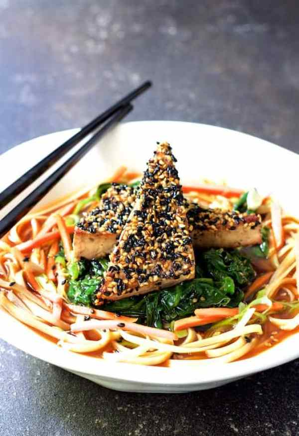 Sesame Tofu with Spinach and Rice Noodles in Ginger Broth - Close-up in white bowl with black chopsticks on gray background