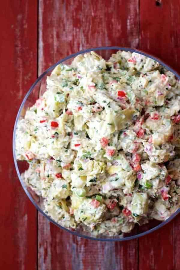 Potato Artichoke Salad with Horseradish Dressing - Overhead shot of salad on red distressed surface