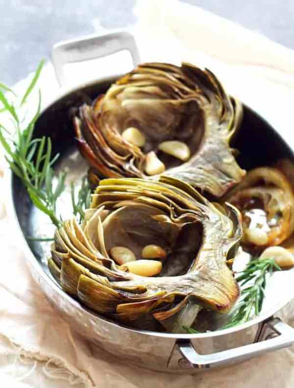 Oven Roasted Artichokes with Roasted Garlic Butter - Hero shot in roasting pan garnished with herb sprigs