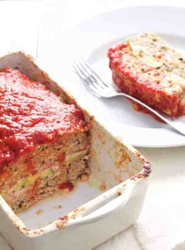 Layered Turkey Meatloaf with Roasted Red Pepper Sauce - Shot of interior or meatloaf with most of it still in white baking dish and a slice off to the side on white plate
