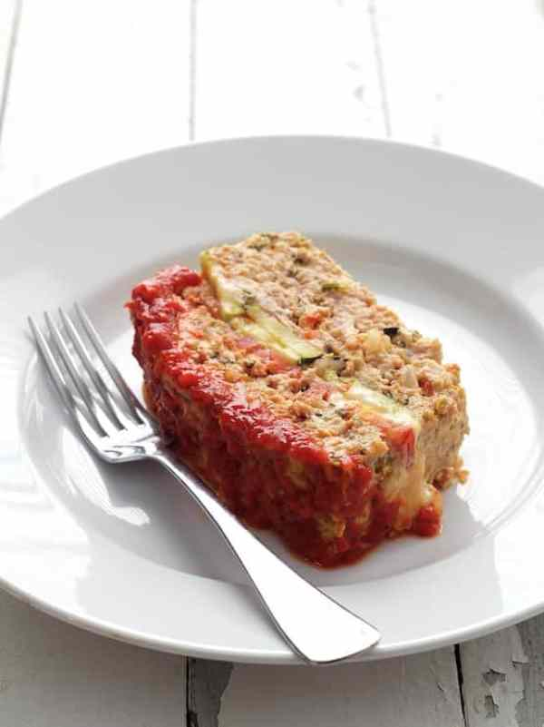 Layered Turkey Meatloaf with Roasted Red Pepper Sauce - Slice of meatloaf on white plate on white background