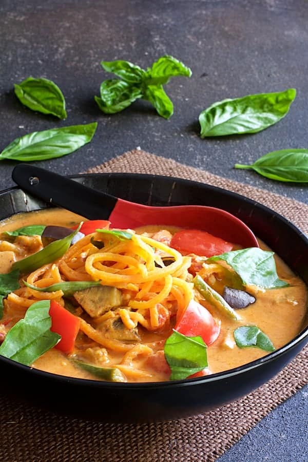 Thai Red Curry with Vegetables and Sweet Potato Noodles - Close-up straight-on shot of curry in black bowl with red and black porcelain spoon garnished with fresh basil