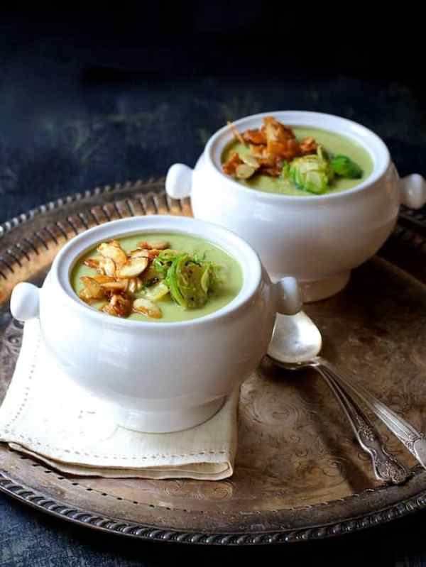 Cream of Brussels Sprouts Soup with Butter and Turbinado Roasted Almonds - Hero shot of two bowls of the soup on serving platter