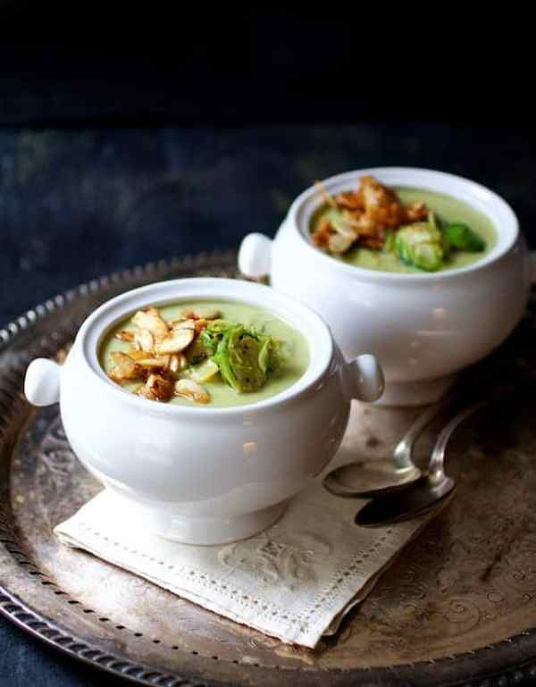 Cream of Brussels Sprouts Soup with Butter and Turbinado Toasted Almonds - Two bowls of the soup on serving platter with one on an embroidered napkin