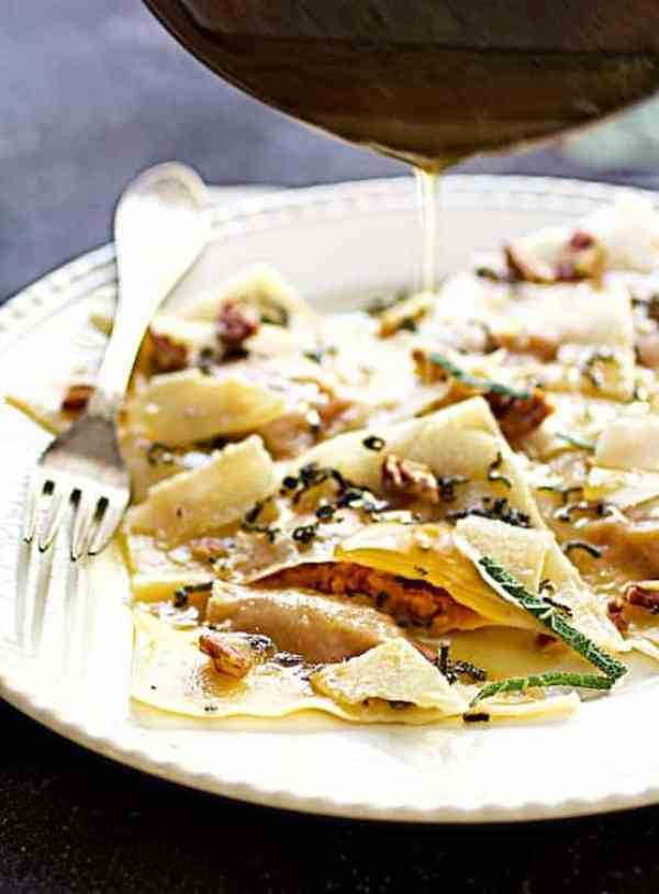 Pumpkin Ravioli with Sage Brown Butter Parmesan and Pecans - Hero shot of butter being poured over ravioli on white plate