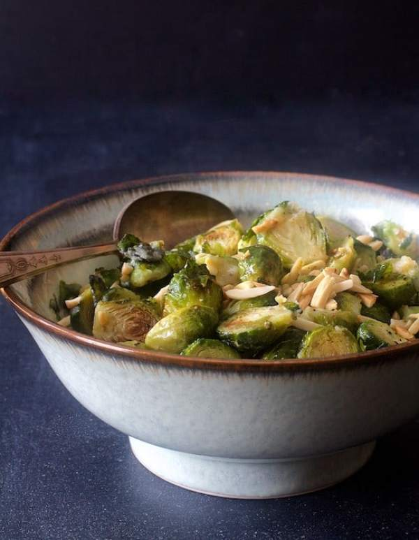 Roasted Brussels Sprouts with Browned Butter and Almonds in serving bowl with serving spoon on dark blue background
