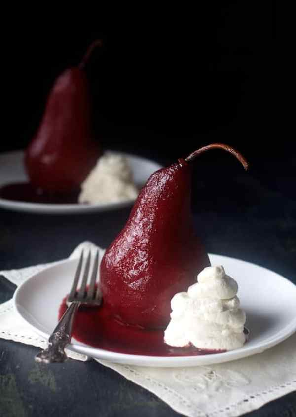 Spiced Red Wine-Poached Pears with Vanilla Mascarpone Whipped Cream - Pears on white plate with mascarpone cream