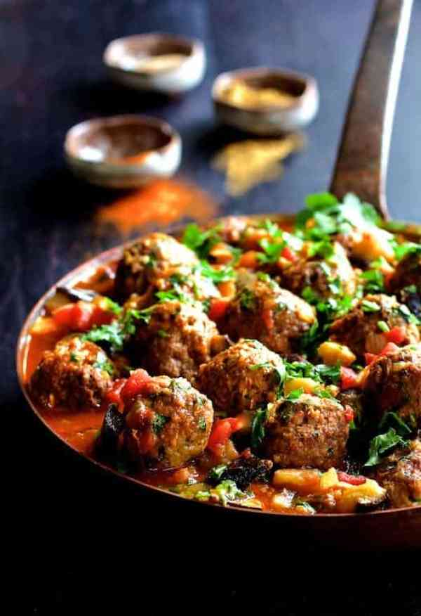 Moroccan Meatball and Vegetable Ragout - Hero shot of dish in saute pan on blue background with three small spice bowls in the background