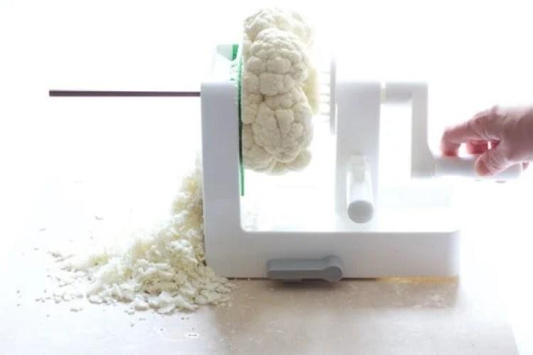 Photo of cauliflower being shredded in a vegetable spiralizer