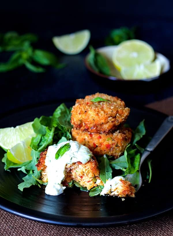 Thai Salmon Cakes with Basil - Lime Mayonnaise - Close-up shot of salmon cakes on black plate garnished with lime wedges