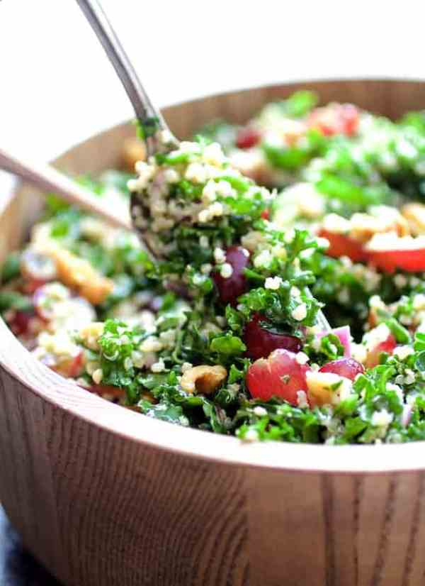 Quinoa and Kale Salad with Red Grapes, Walnuts and Honey - Lemon Dressing - Straight-on shot of salad being served with silver utensils