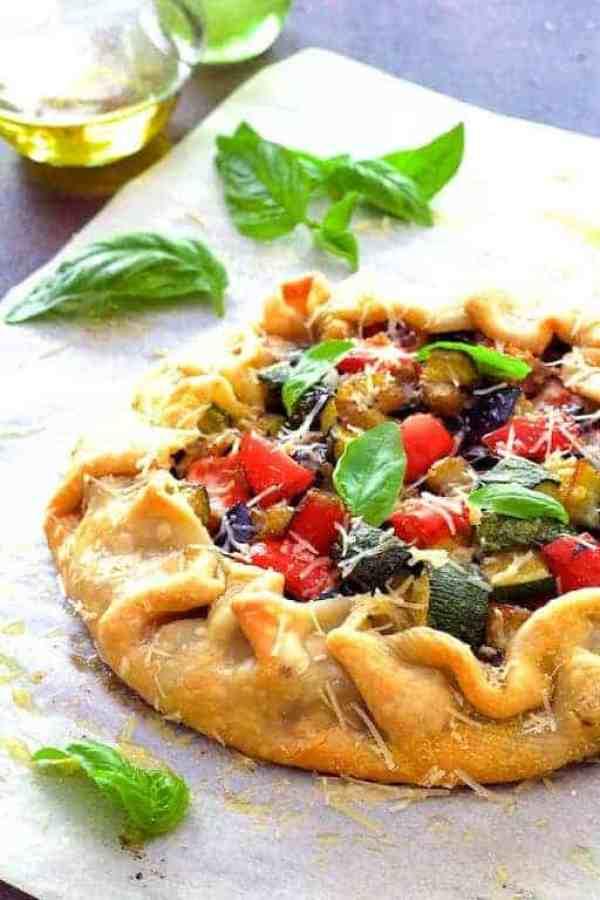 Mediterranean Roasted Vegetable Galette - Hero shot of galette on parchment paper garnished with fresh basil