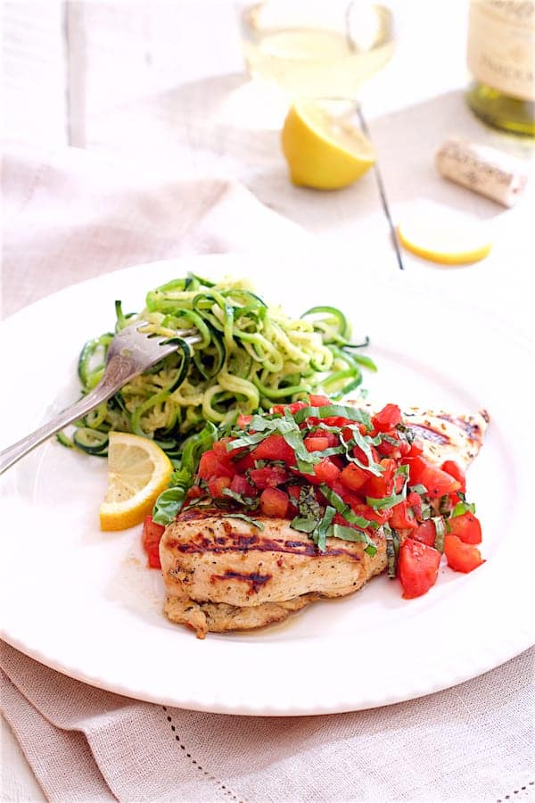 Bruschetta Chicken with Zucchini Noodles - On white plate with lemons and wine in the background