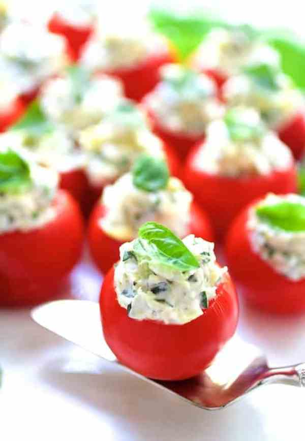 Cheese and Artichoke Stuffed Tomatoes and Grilled Zucchini - Filled tomato on server garnished with basil leaf