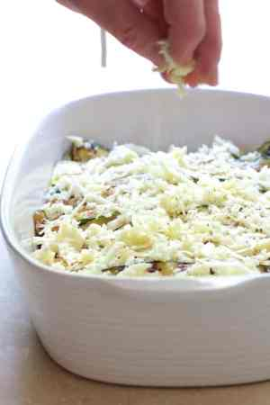 Layered Zucchini Corn Casserole - Cheese being sprinkled over casserole