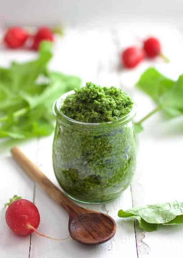 Radish Greens Pesto - In glass jar on white distressed surface with small wooden spoon on the side