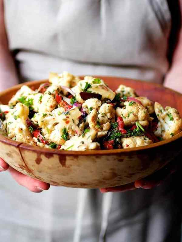 Warm Roasted Cauliflower and Chickpea Salad - Shot of cook holding the bowl of salad in wooden bowl