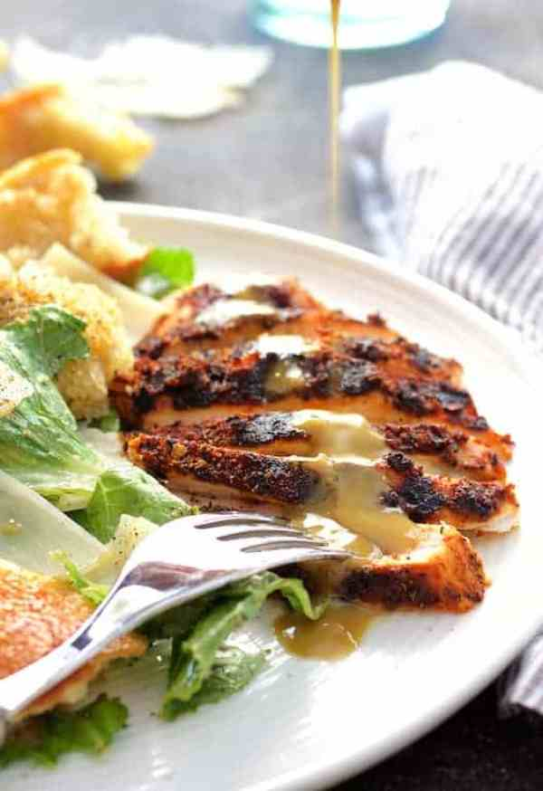 Blackened Chicken Caesar Salad - Hero shot of salad with dressing being drizzled over chicken