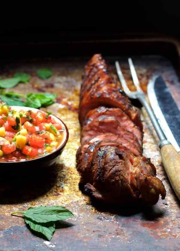 Bourbon Marinated Pork Tenderloin with Peach Watermelon Salsa - Another straight-on shot of pork with salsa with mint leaves scattered around with meat fork and butcher knife