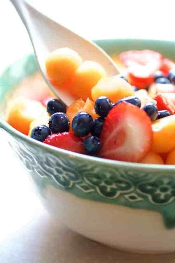 Summer Fruit Salad with Orange Yogurt Vanilla Dressing - Close-up of salad being stirred with white spoon
