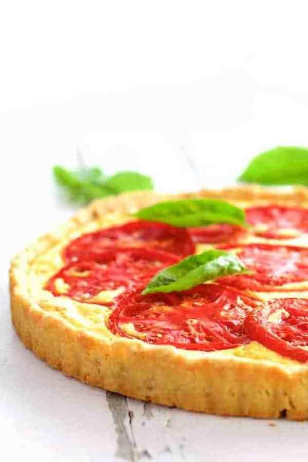 Tomato Ricotta Tart with Basil Pesto - Straight-on close-up shot of the tart and crust garnished with fresh basil