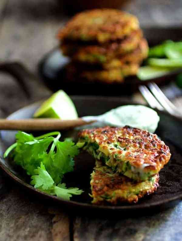 Whole Grain Zucchini Jalapeno Fritters with Cilantro Lime Sour Cream - Fritters cut in half on cast iron pan with spoonful of sour cream in the background