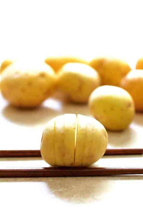 Close-up shot of baby potato on two chopsticks after being hasselbacked
