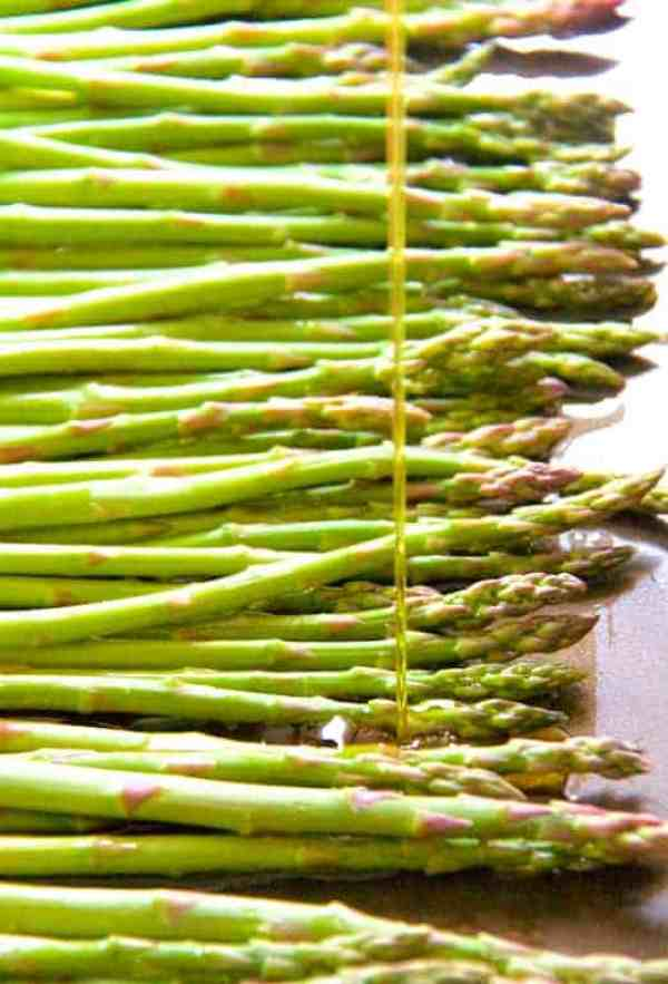 Asparagus being drizzled with oil ready for roasting