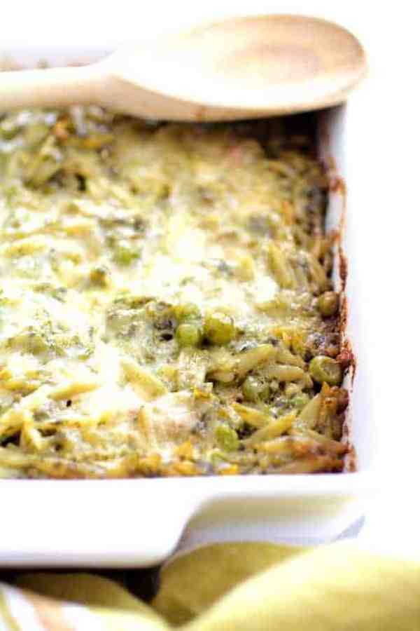 Baked Orzo with Pesto Peas Prosciutto and Mascarpone - Photo of dish before being served from white baking dish