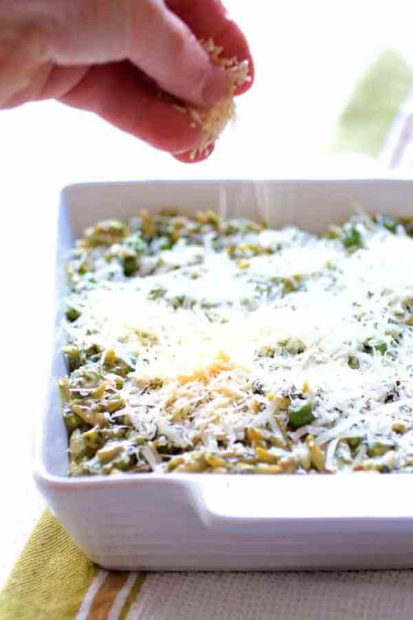 Baked Orzo with Pesto Peas Prosciutto and Mascarpone - Cheese being sprinkled over dish before baking