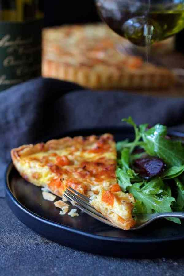 Butternut Squash Leek and Gruyere Tart - A bite of the tart resting on fork while salad is being drizzled with olive oil