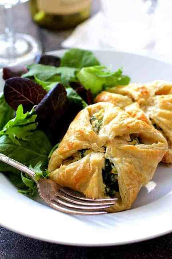 Chicken Spinach and Artichoke Puff Pastry Parcels - Hero shot on white plate with salad greens